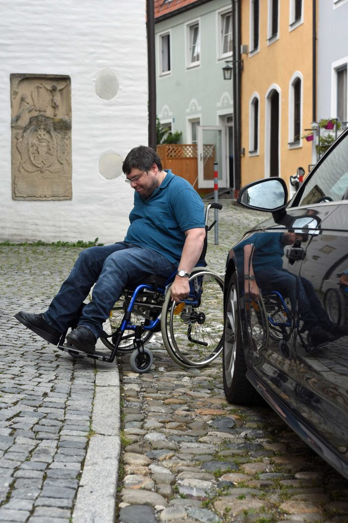 Ein Mann versucht mit einem Rollstuhl über einen steinigen Pflasterbelag zu fahren.