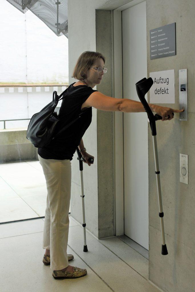"""Eine Frau mit Krücken steht vor einem Aufzug mit dem Schild """"Aufzug defekt"""""""