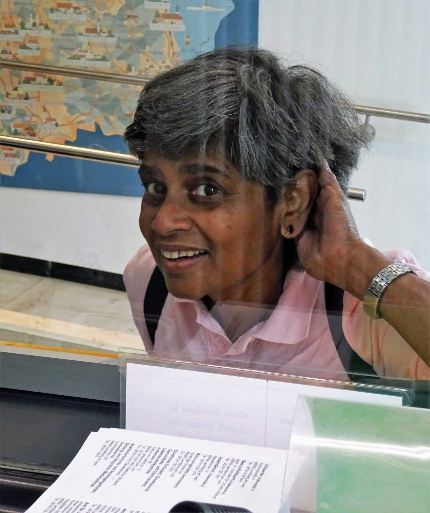 Eine Frau steht hinter einer Scheibe und versucht mit der Hand die Geräusche abzuschirmen.