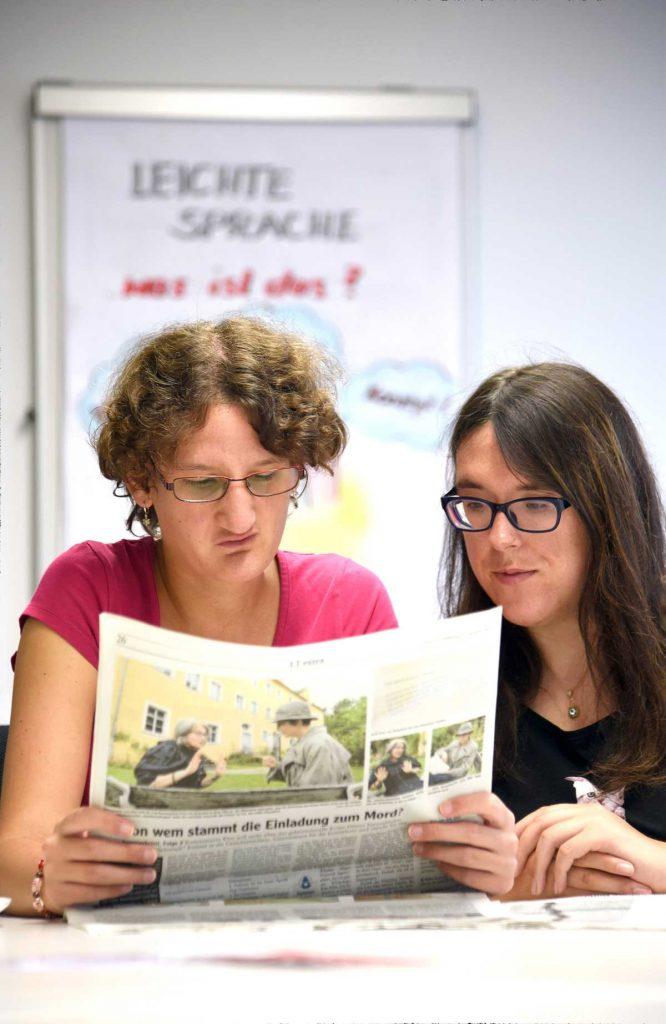 Zwei Frauen versuchen eine Zeitung zu lesen.