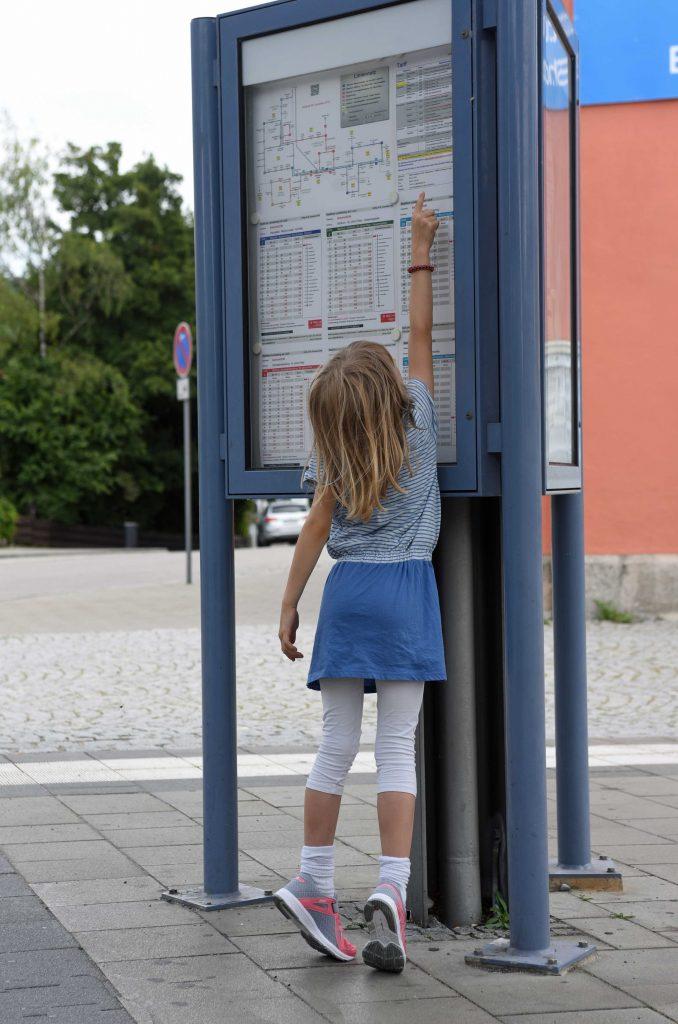 Ein kleines Mädchen steht auf dem Zehenspitzen um den Busplan zu lesen.