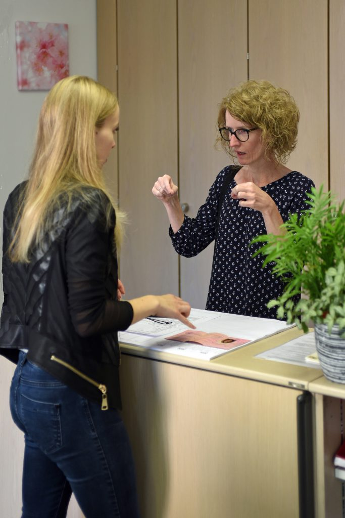 Zwei Frauen stehen an einem Schalter, eine versucht mit Gestiken etwas zu erklären.
