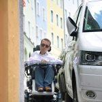 Ein Rollstuhlfahrern hat zu wenig Platz zwischen der Hauswand und einem parkendem Auto