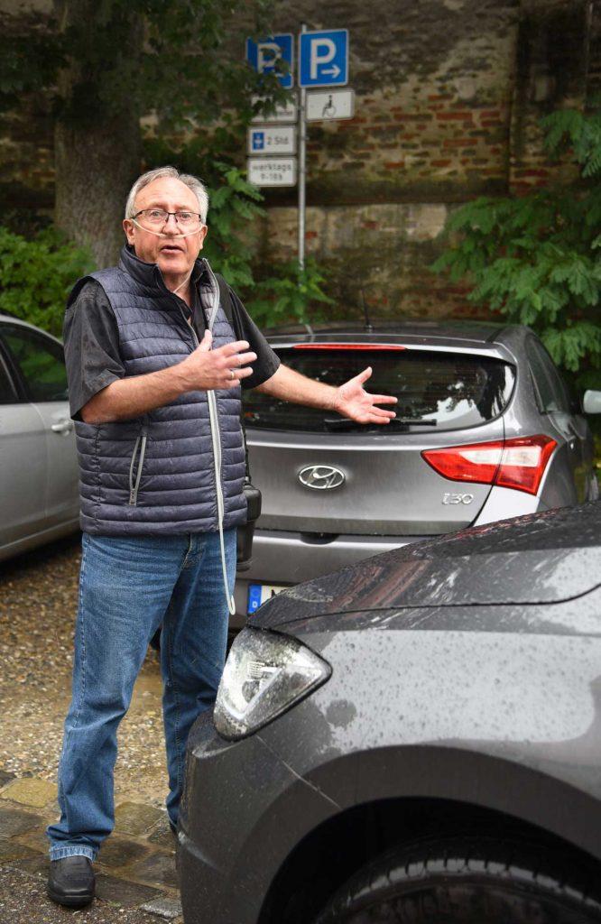 Ein älterer Mann steht vor einem bereits belegten Parkplatz.