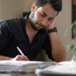 Ein junger syrischer Mann sitzt vor einem Haufen Formulare.