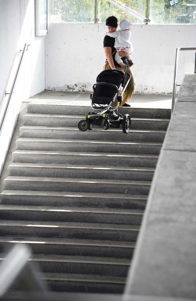 Eine Frau hat ihr Baby auf dem Arm um den Kinderwagen die Treppe herunterzutragen.