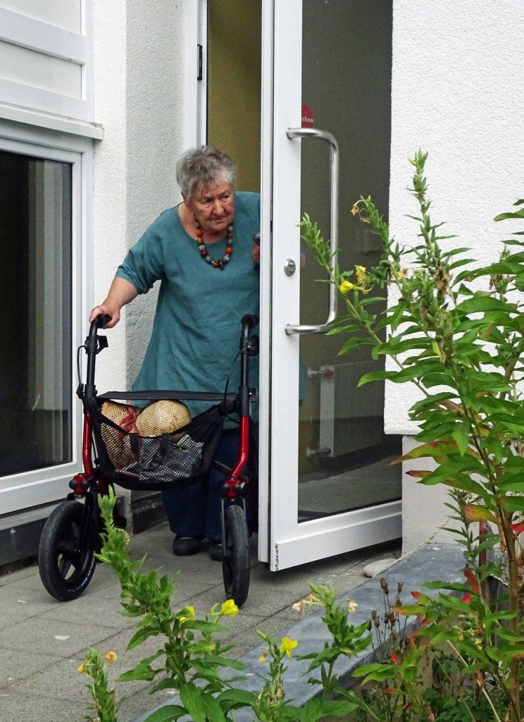 Eine ältere Frau hält mit einer Hand die Türe auf, während sie mit der anderen ihren Rollator schiebt.