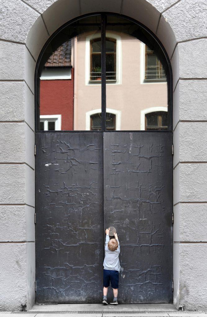 Ein 5-jähriges Kind versucht eine große Stahltür zu öffnen.